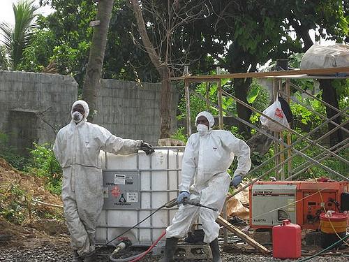 Arbeiter ziehen Schutzanzüge an, um Haina zu reinigen.  Schmiede-Institut / Flickr