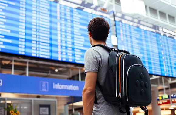 via Shutterstock / Traveler Guardando Airport Flight Monitor