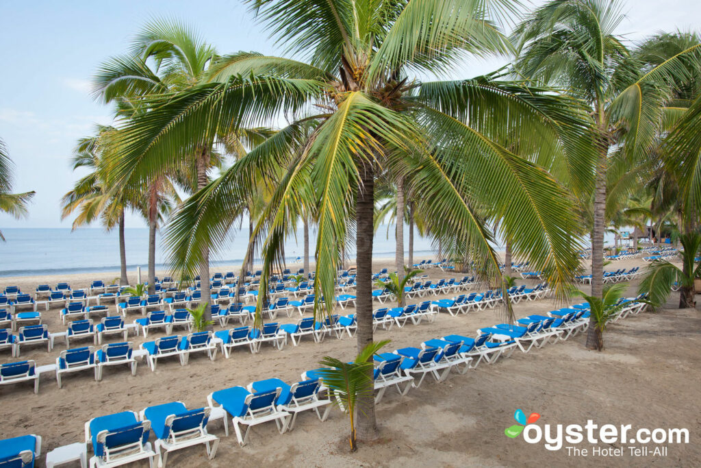 Beach chairs and palm trees at Riu Palace Pacifico All Inclusive in Riviera Nayarit