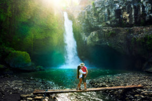 Couple kissing in front of waterfall