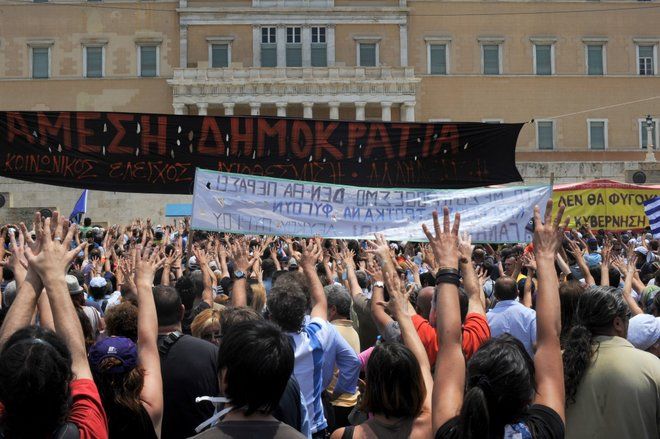Greeks protesting in front of Parliament using the mountza gesture; Courtesy of Ggia, Wikimedia Commons
