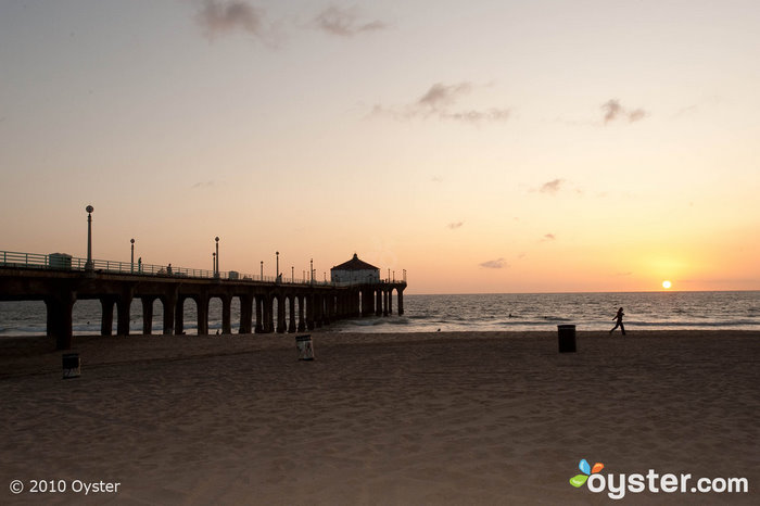 Locals and tourists fish from the pier on Manhattan Beach while they watch the sunset.
