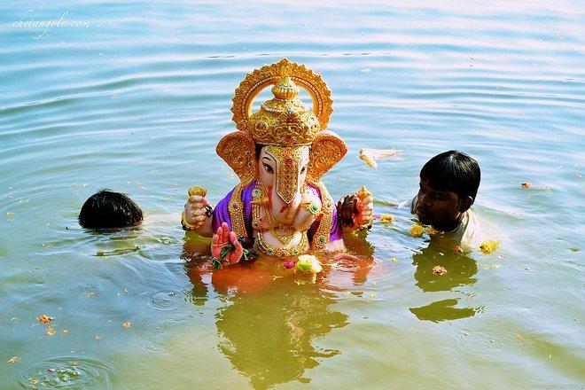 Submergindo uma estátua de Ganesh durante Ganesh Chaturthi. Cortesia de Chetan Gole / Wikimedia Commons .