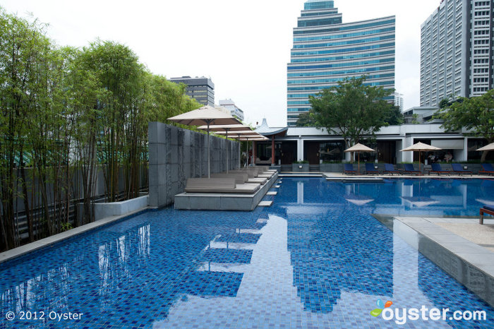 The serene outdoor pool is surrounded by pagoda-style cabanas.