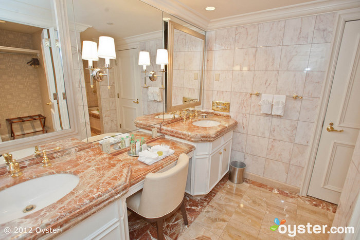 Luxurious marble bathrooms have large vanities for getting ready for a night out.