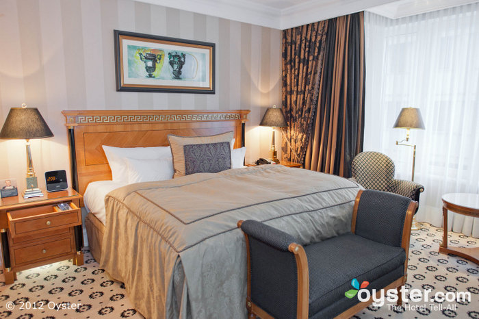 Elegant rooms have mahogany furniture, rich curtains and plush bedding.
