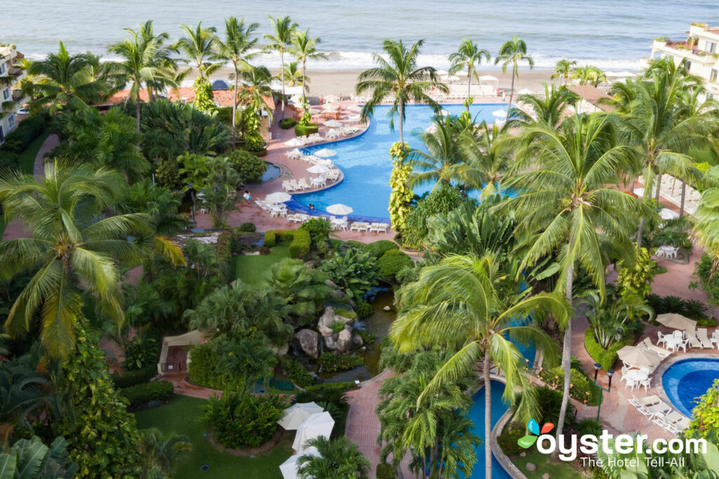 The pool and beach with palm trees at Velas Vallarta