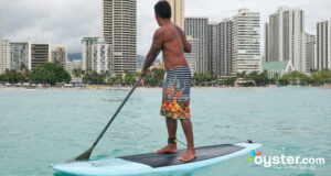 A surfer balances atop his board at Waikiki Beach, Oahu