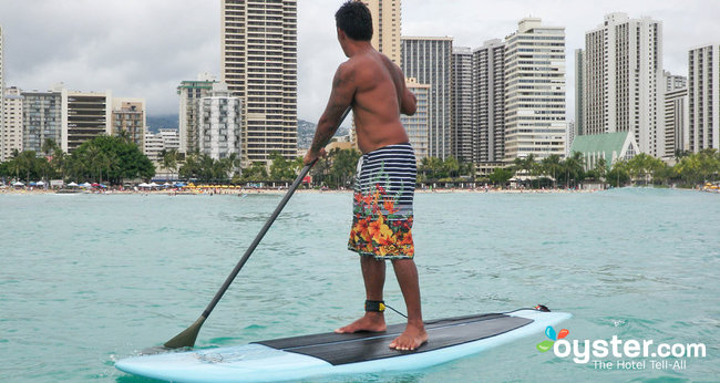 Un surfeur se balance au sommet de sa planche à Waikiki Beach, Oahu