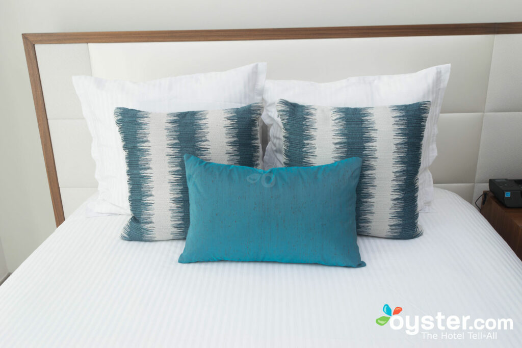 Uma cama no Secrets the Vine Cancun Resort e Spa.