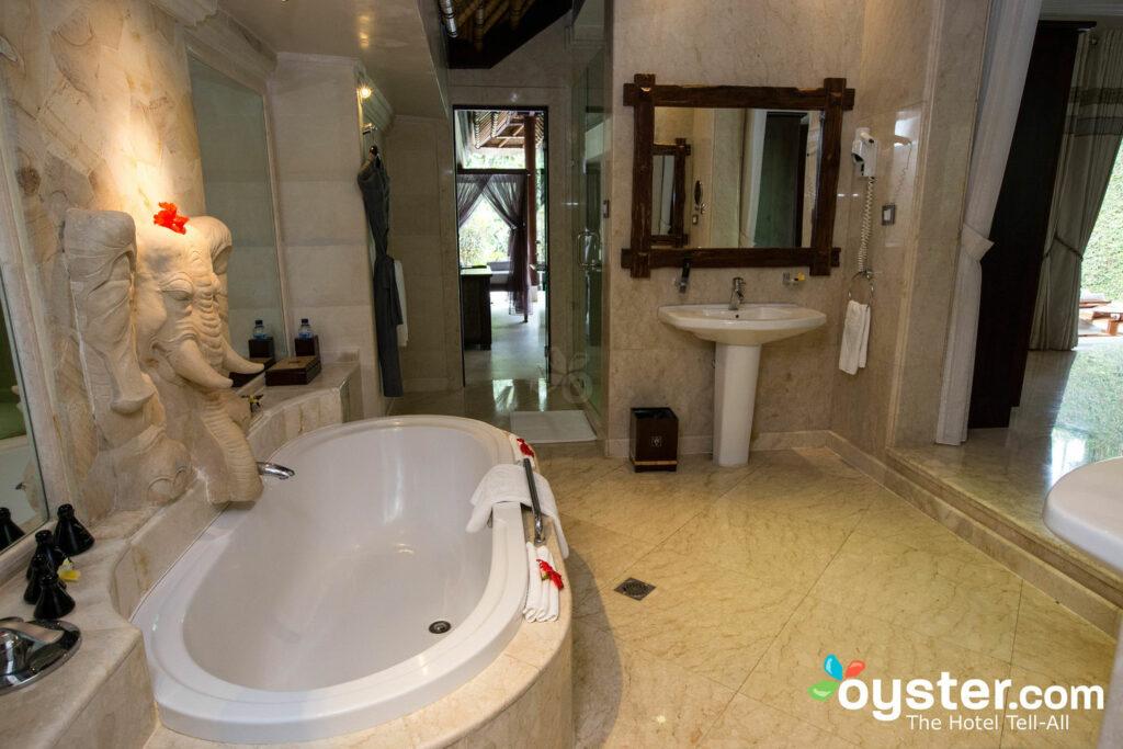 Die Zimmer sind für Romantik mit wunderschönen indonesischen Elementen (wie der geschnitzte Elefant oben) und massiven Badezimmern mit tiefen Badewannen vorbereitet.
