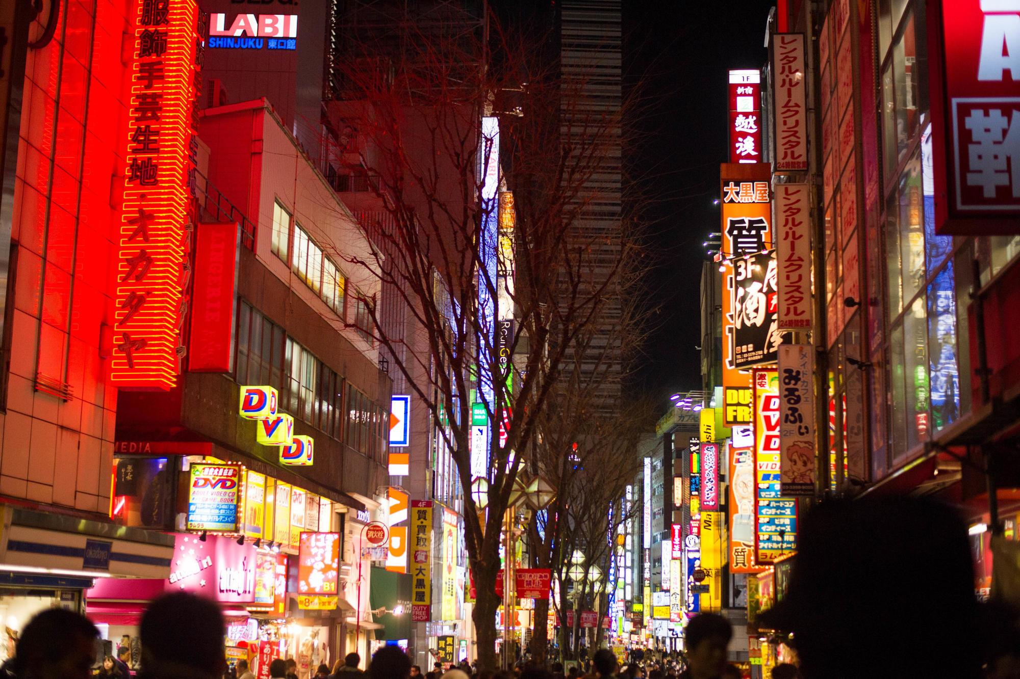 Shinjuku's neon-lit, crowded streets at night in Tokyo