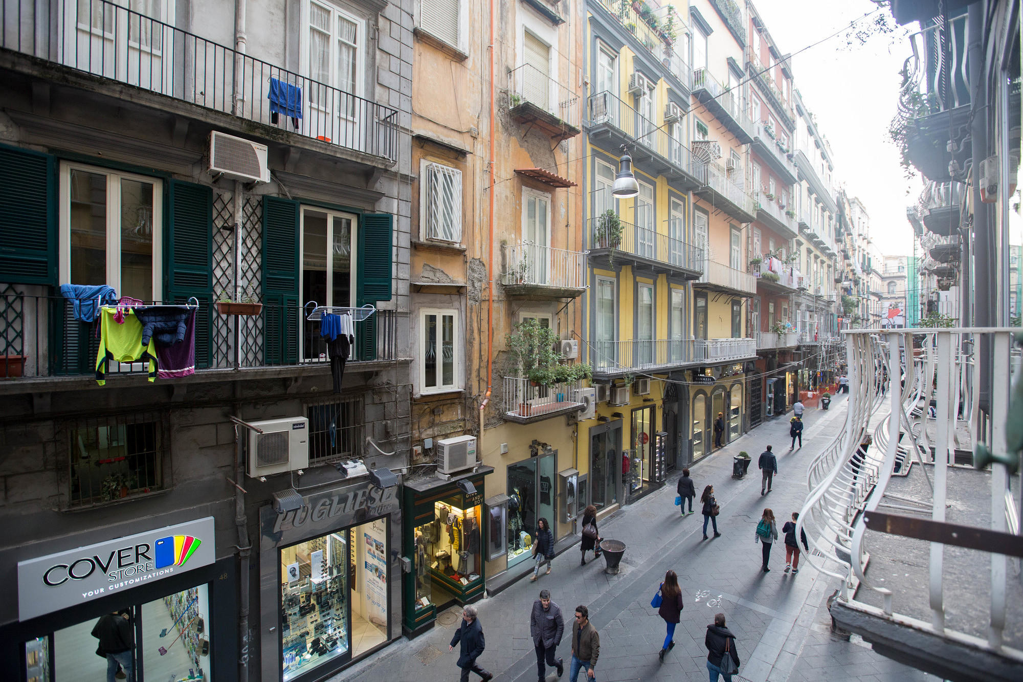 Narrow pedestrian streets lined with shops and restaurants in Naples' historic city center.