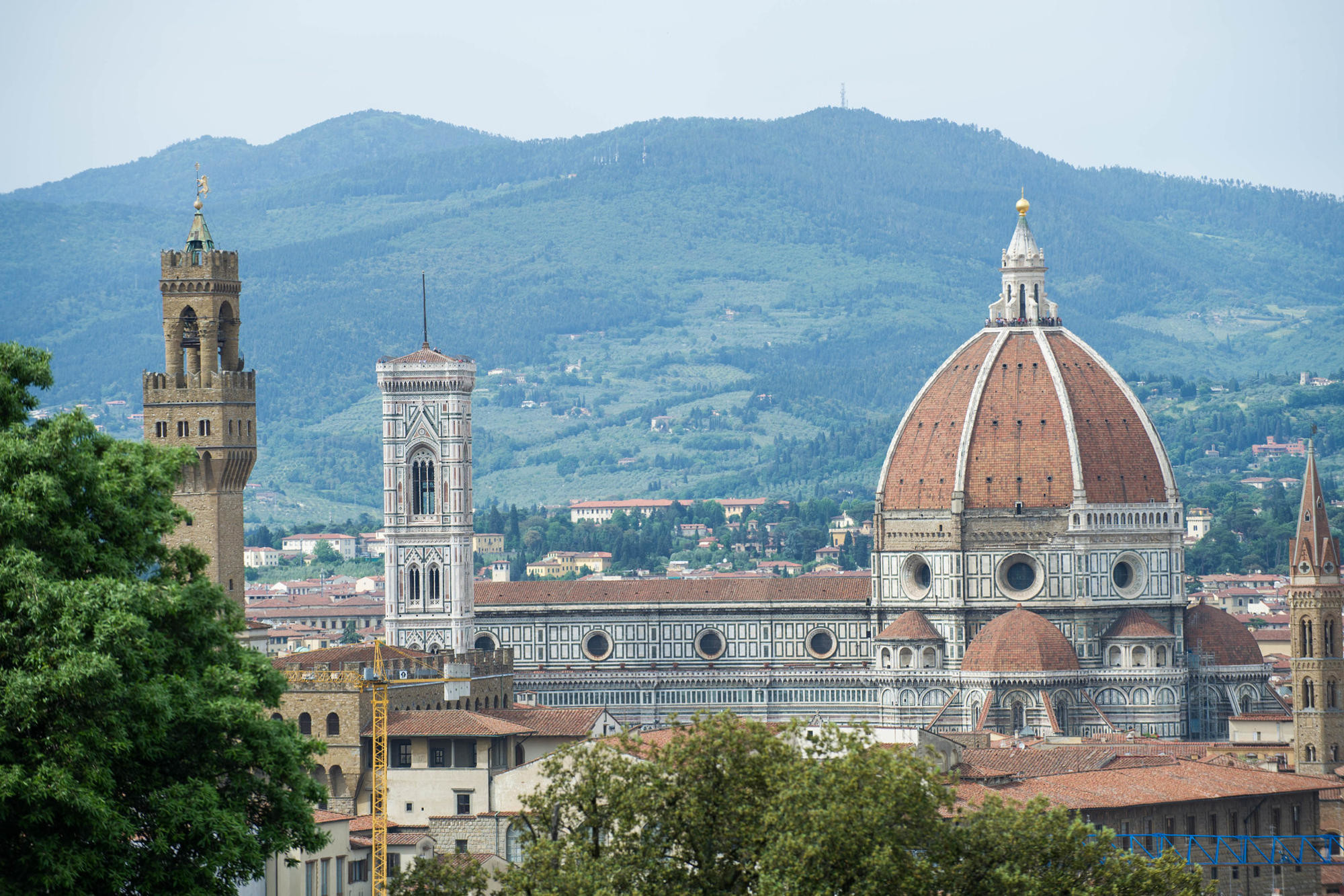 The dome and campanile of the Duomo in Florence, with Tuscan hills in the background.