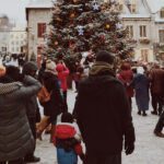 Christmas tree with people around in a city square
