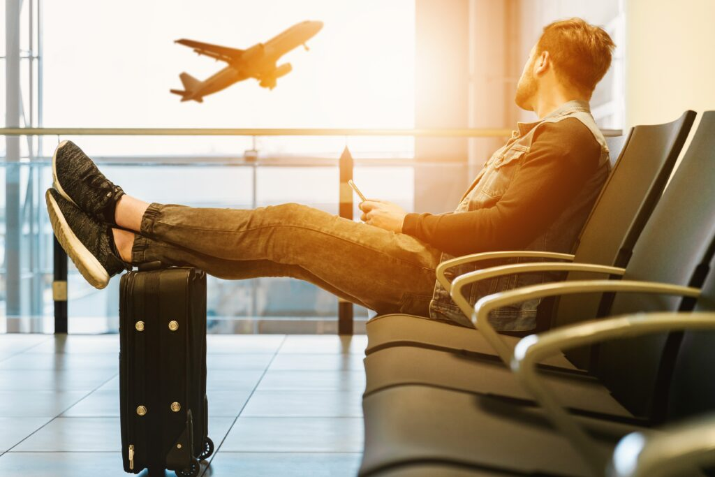 Man waiting at the airport with his suitcase