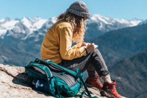 Woman journaling on a mountain