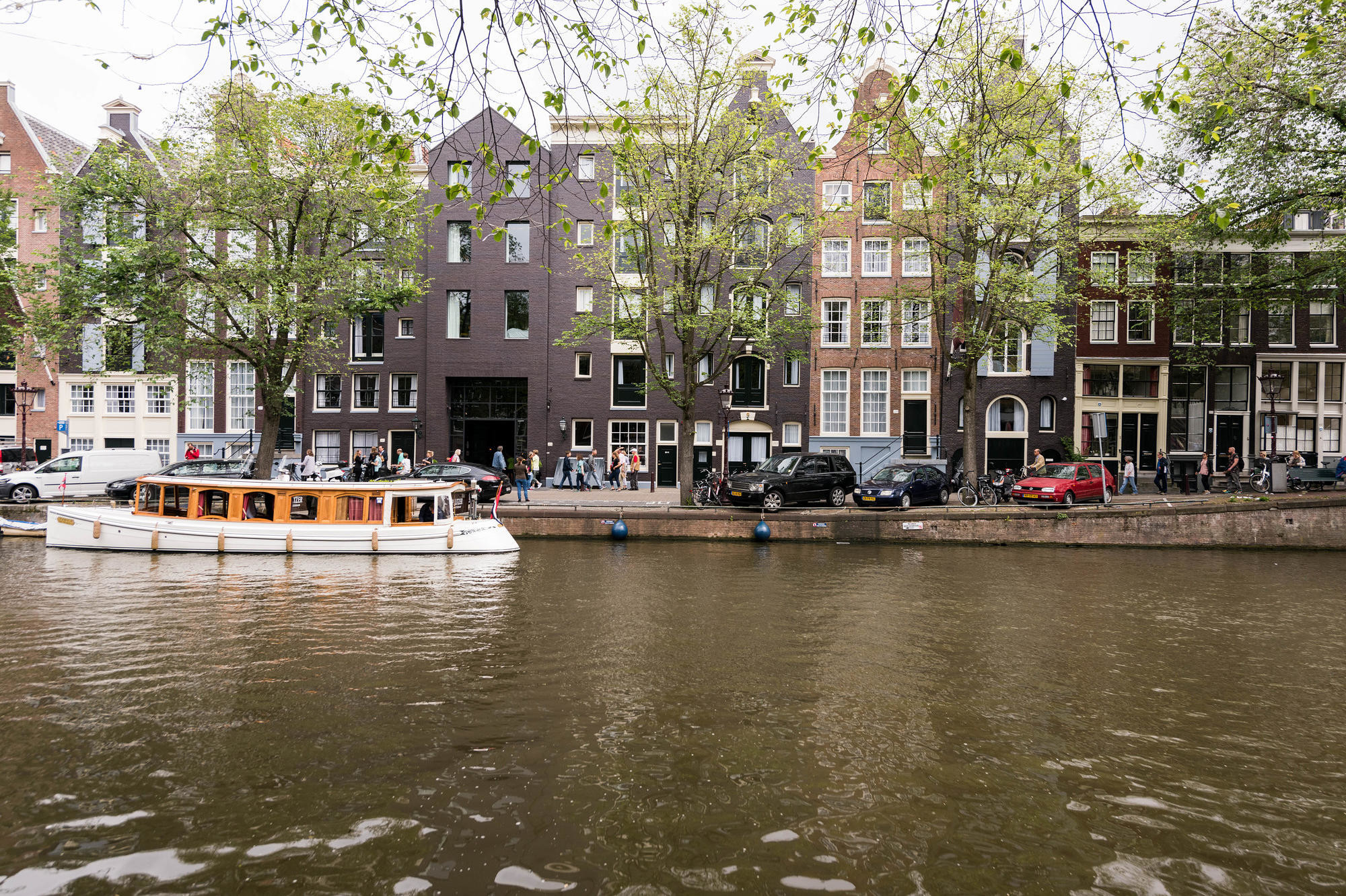 Canal and view of the Pulitzer Hotel with boats in Amsterdam