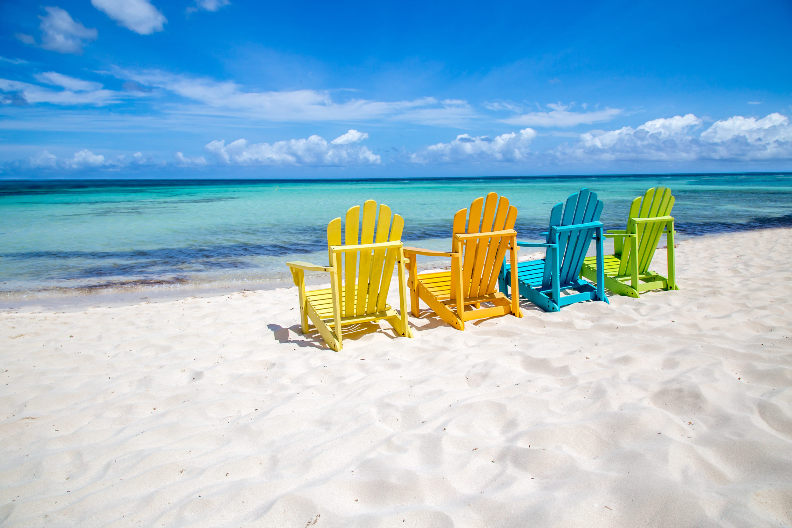 Four colorful beach chairs on a beach