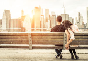 Couple sitting on a bench holding hands in front of the New York City skyline
