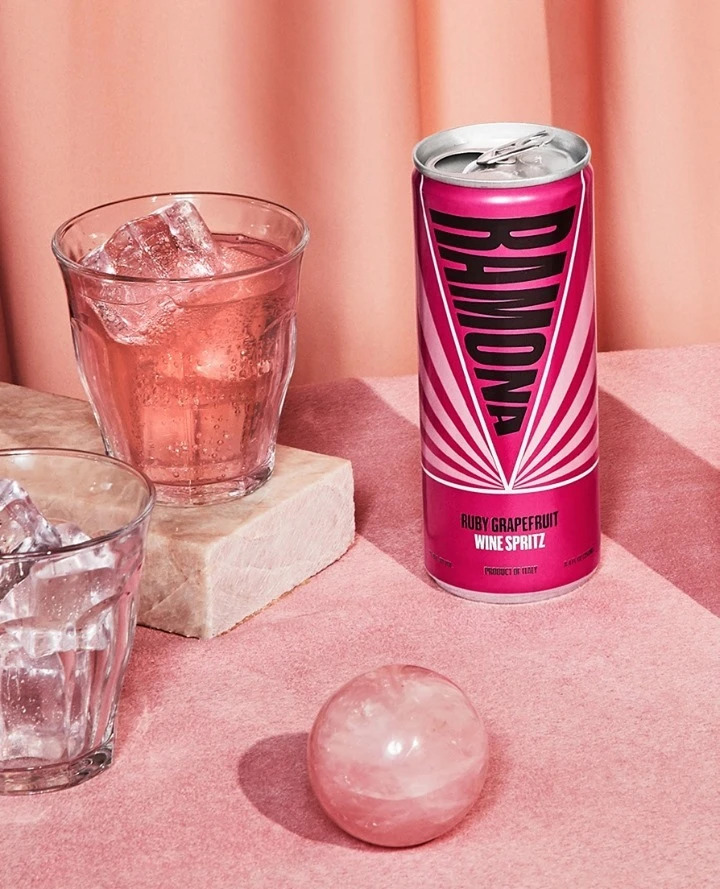 Can of Romona Ruby Grapefruit Wine Spritz and a full tumbler glass on a pink table