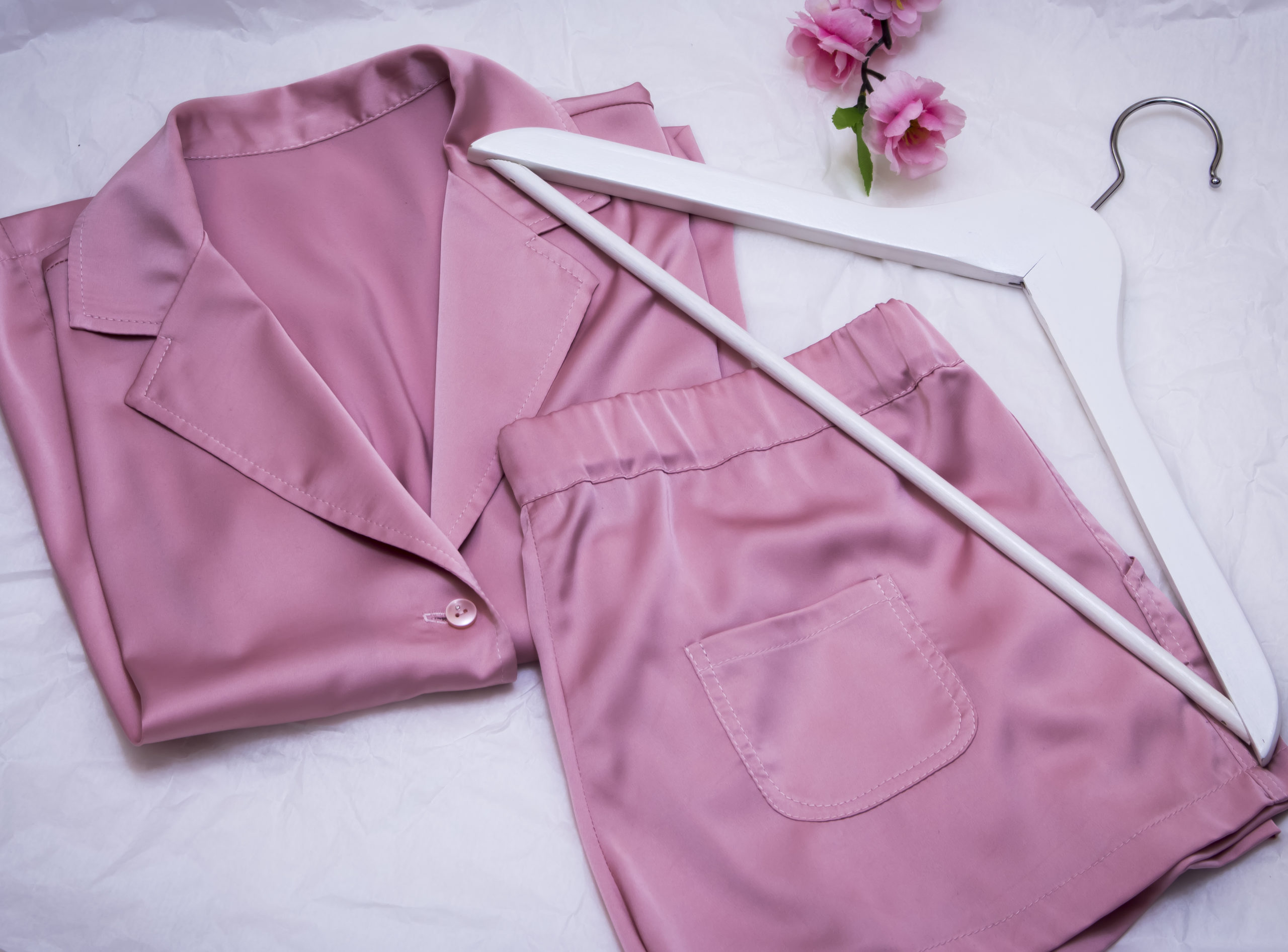 A set of pink silk pajamas laid out on a bed next to a clothing hanger and a flower