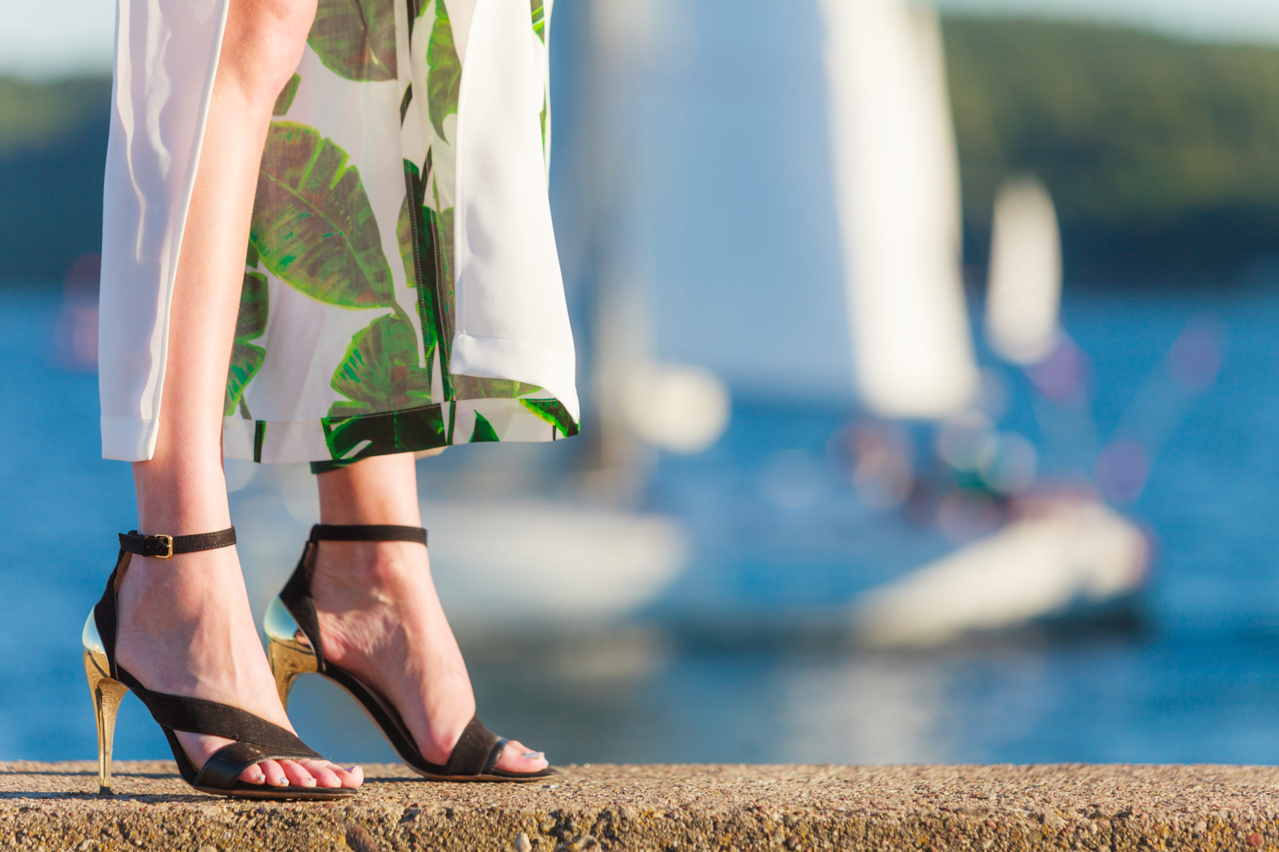Woman wearing high heeled sandals, standing in front of a body of water with sailboats on it